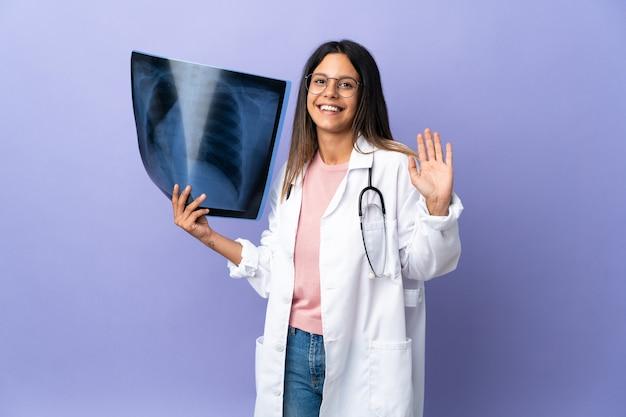 Jeune médecin femme tenant une radiographie saluant avec la main avec une expression heureuse
