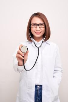 Jeune médecin femme tenant stéthoscope isolé sur blanc