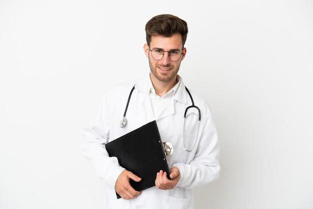Jeune médecin homme de race blanche sur isolé sur fond blanc portant une robe de médecin et tenant un dossier