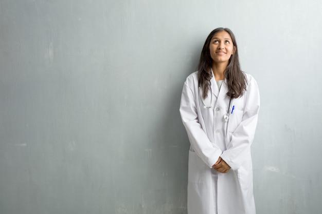 Jeune médecin indien femme contre un mur en levant, en pensant à quelque chose d'amusant et d'avoir une idée