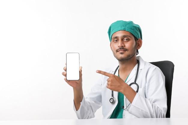 Jeune médecin indien montrant l'écran du smartphone sur fond blanc.