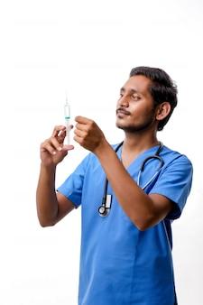 Jeune médecin indien tenant une seringue chargée à la main sur fond blanc.