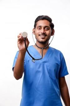 Jeune médecin indien tenant un stéthoscope à la main sur fond blanc.