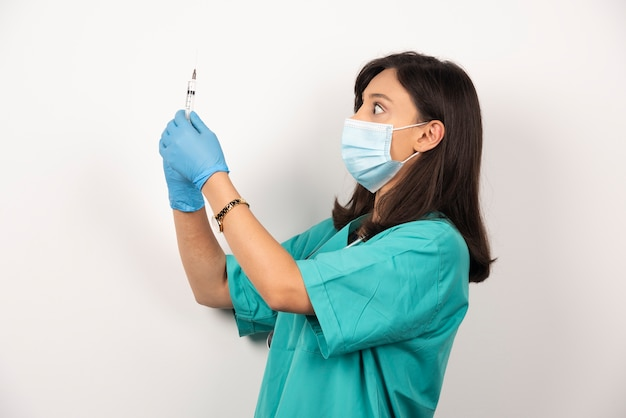 Jeune médecin en masque médical et gants tenant la seringue sur fond blanc.