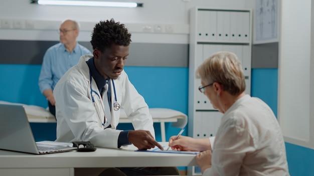 Jeune médecin montrant un fichier à un vieux patient pour signature