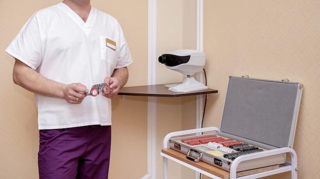 Jeune médecin optométriste debout près de l'équipement de diagnostic