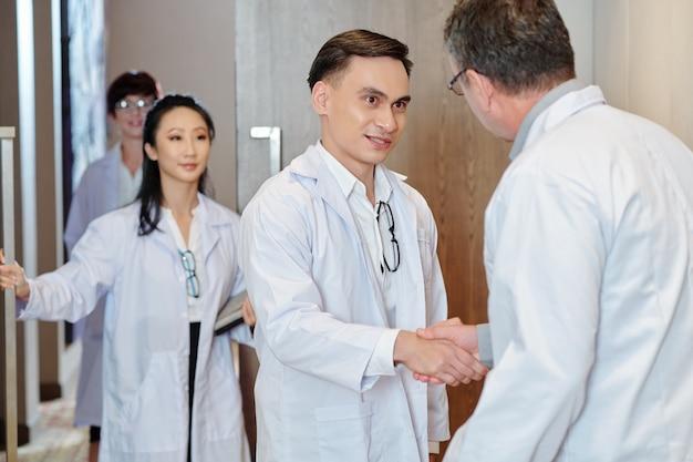 Jeune médecin parlant à un collègue expérimenté après une conférence ou une conférence et en serrant la main