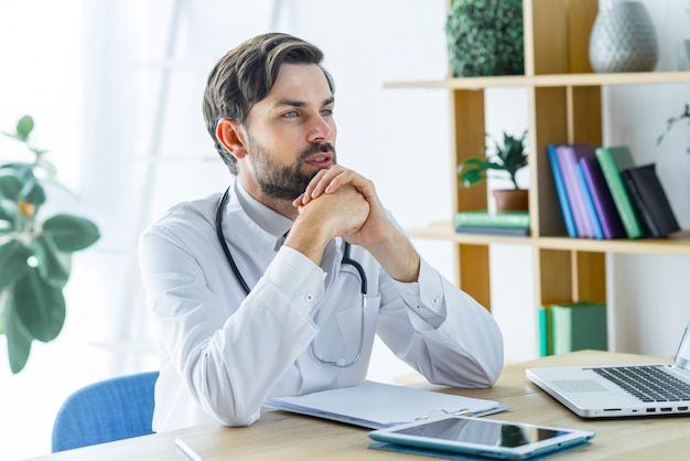 Jeune médecin pensant au bureau