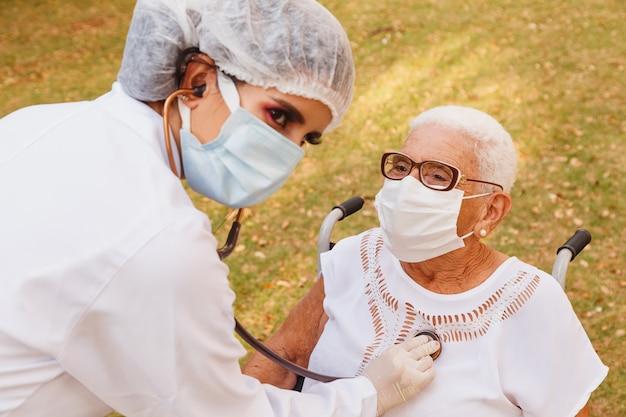 Jeune médecin prenant soin d'une femme âgée dans le parc