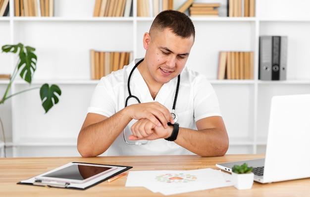 Jeune médecin regarde sa montre