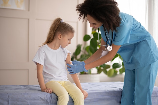 Jeune médecin s'assurant qu'une petite fille va bien après la vaccination