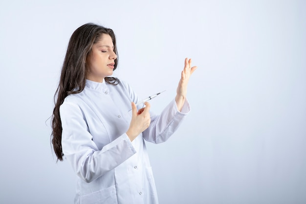 Jeune médecin avec une seringue se prépare pour l'injection sur un mur blanc.