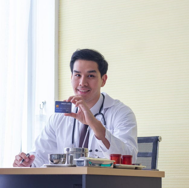 Jeune médecin de sexe masculin asiatique sourit montrant la carte de crédit sur le bureau dans un hôpital