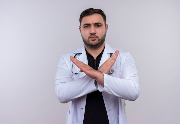 Jeune médecin de sexe masculin barbu portant blouse blanche avec stéthoscope faisant panneau d'arrêt traversant les bras