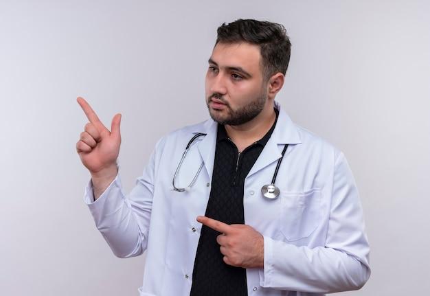 Jeune médecin de sexe masculin barbu portant un manteau blanc avec stéthoscope à côté avec une expression confiante sérieuse pointant vers le côté