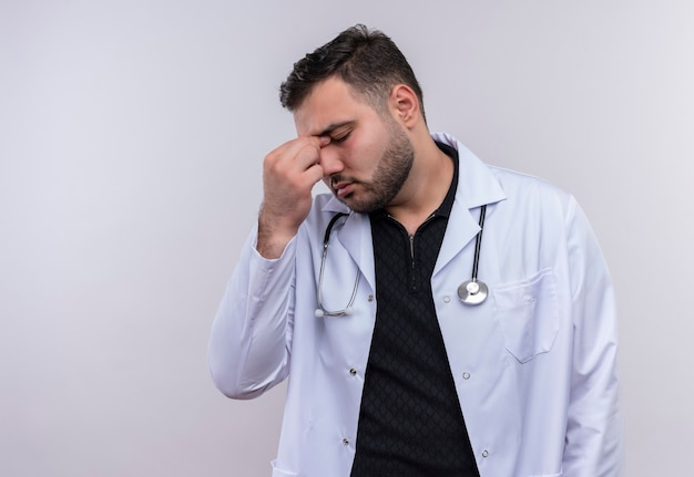 Jeune médecin de sexe masculin barbu portant un manteau blanc avec stéthoscope à la fatigue et l'ennui toucher le nez entre les yeux fermés
