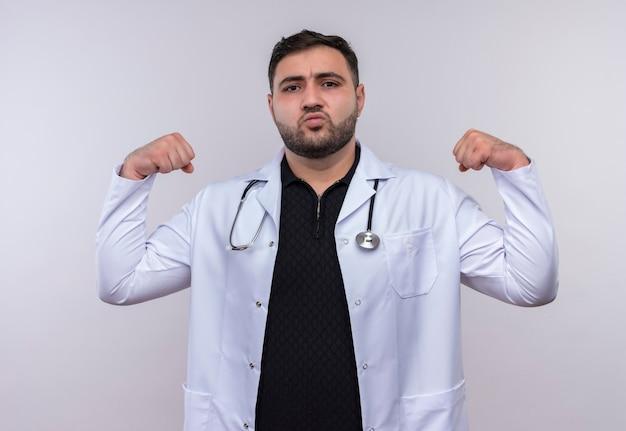 Jeune médecin de sexe masculin barbu portant un manteau blanc avec stéthoscope posant comme athlète avec le poing fermé montrant les biceps, le concept gagnant