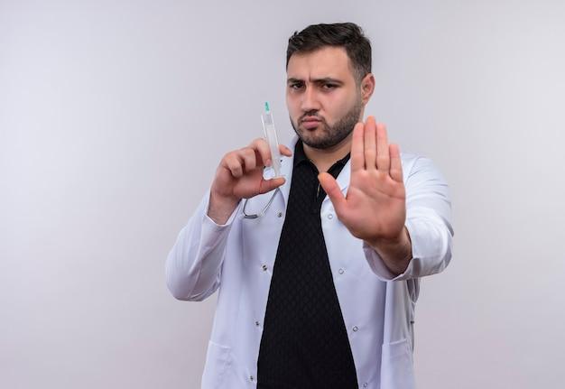 Jeune médecin de sexe masculin barbu portant un manteau blanc avec stéthoscope tenant la seringue faisant panneau d'arrêt avec la main avec un visage fronçant les sourcils