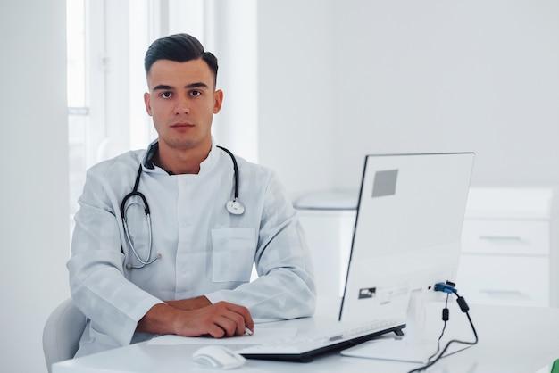 Un jeune médecin de sexe masculin élégant avec stéthoscope est en clinique pendant la journée.
