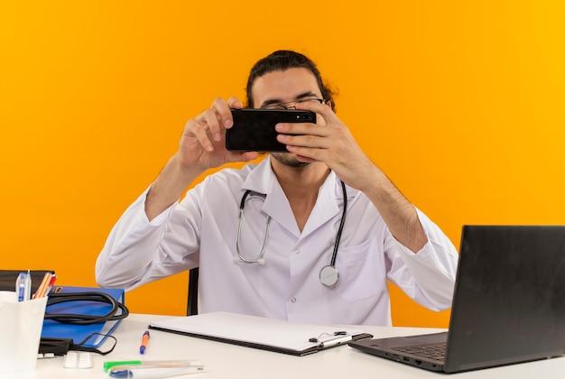 Jeune médecin de sexe masculin avec des lunettes médicales portant une robe médicale avec stéthoscope assis au bureau