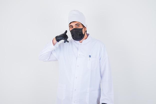 Jeune médecin de sexe masculin montrant le geste de l'appel en uniforme blanc et l'air confiant. vue de face.