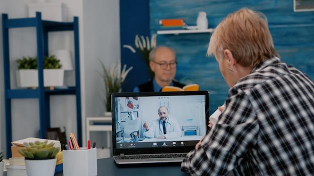 Jeune médecin de sexe masculin parlant à une patiente âgée par télémédecine en ligne