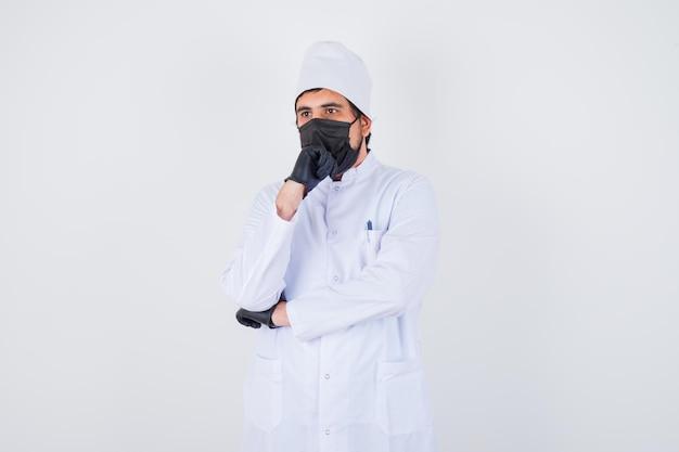 Jeune médecin de sexe masculin soutenant le menton sur le poing en uniforme blanc et l'air réfléchi. vue de face.