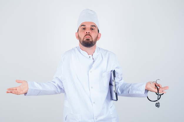 Jeune médecin de sexe masculin tenant le presse-papiers et le stéthoscope, montrant un geste impuissant en uniforme blanc et regardant perplexe, vue de face.