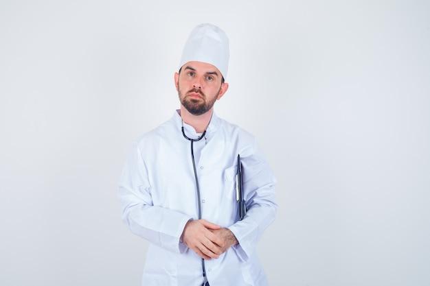 Jeune médecin de sexe masculin tenant le presse-papiers en uniforme blanc et regardant grave, vue de face.