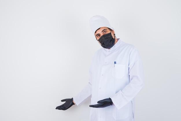 Jeune médecin de sexe masculin en uniforme blanc faisant semblant de montrer quelque chose et ayant l'air confiant, vue de face.