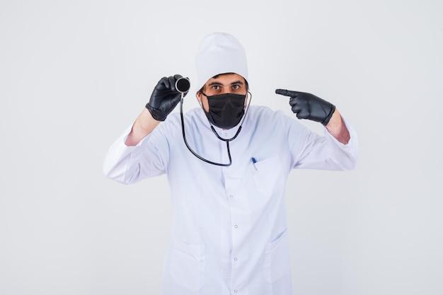 Jeune médecin de sexe masculin en uniforme blanc pointant le stéthoscope et l'air confiant, vue de face.