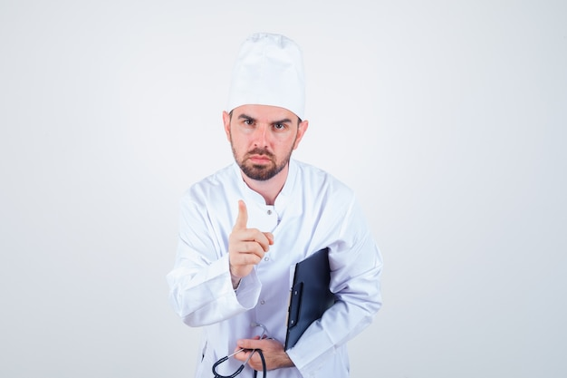 Jeune médecin de sexe masculin en uniforme blanc tenant le presse-papiers, stéthoscope, avertissement avec le doigt et à la grave, vue de face.