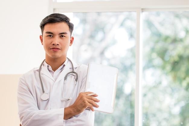Jeune médecin de sexe masculin utilisant une tablette à la recherche d'une caméra avec une robe blanche portant un stéthoscope sur le cou pour rechercher des informations traitant des patients à l'hôpital ou à la clinique, concept médical de soins de santé