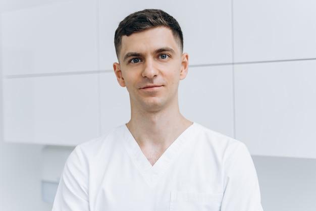 Un jeune médecin de sexe masculin, vêtu de vêtements légers, regarde directement dans la caméra. dentiste mignon isolé sur un mur blanc.