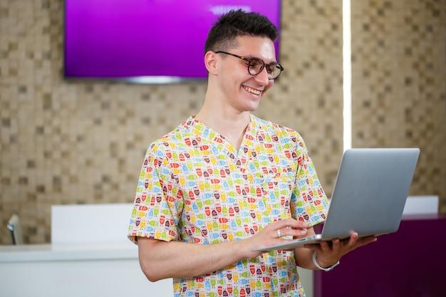 Un jeune médecin travaille sur un ordinateur portable sur une thèse. le médecin de la clinique procède à l'accueil des patients en ligne