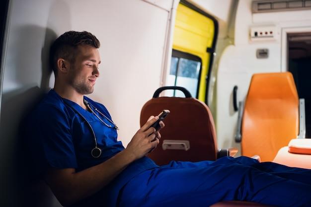Jeune médecin en uniforme bleu se reposant et discutant avec quelqu'un au téléphone la nuit