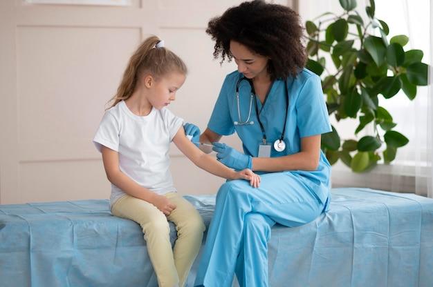 Jeune médecin vaccinant une petite fille