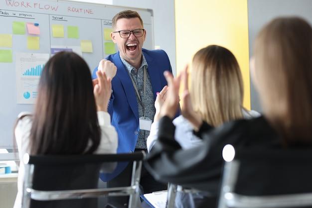 Un jeune mentor masculin émotif organise un briefing commercial avec des collègues