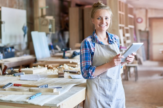 Jeune menuisier à l'aide de tablette numérique dans l'atelier de menuiserie