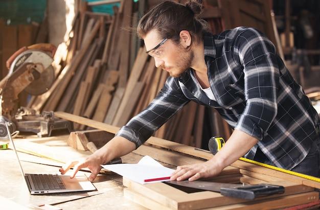 Jeune menuisier avec barbe se penchant sur un établi dans son grand atelier plein de matériel de menuiserie travaillant en ligne avec ordinateur portable