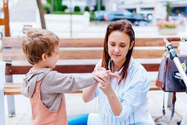 Jeune mère adulte essuyant les mains de son fils dans la rue avec une lingette