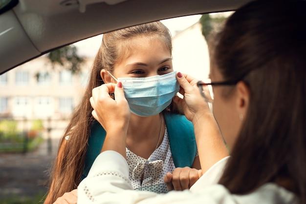 Une jeune mère aide sa fille à mettre un masque de protection avant d'aller à l'école pendant la pandémie