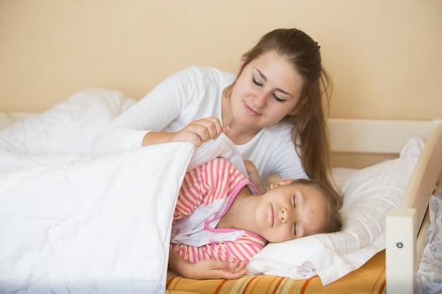 Jeune mère allongée dans son lit avec sa fille et la couvrant d'une couverture