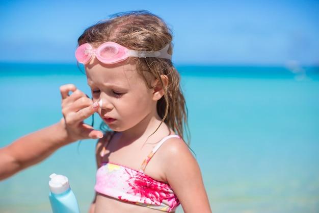 Jeune mère, application de crème solaire sur le nez de sa fille