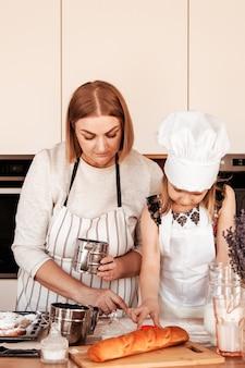 Une jeune mère apprend à sa fille à cuisiner. les parents et les enfants passent du temps ensemble dans la cuisine
