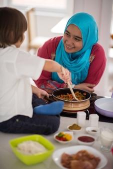 Jeune mère arabe musulmane et petit fils mignon faire de la nourriture et s'amuser dans la cuisine