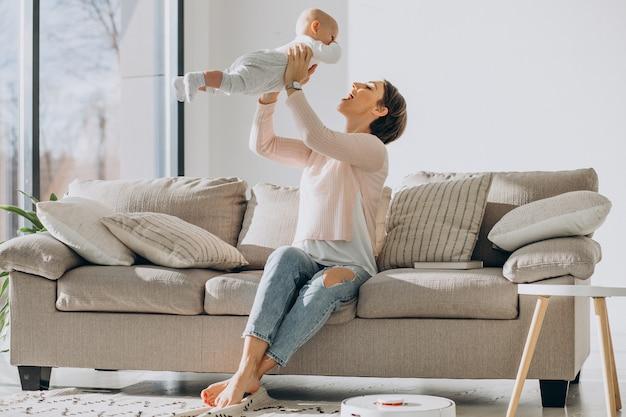 Jeune mère assise sur un canapé avec un fils en bas âge et regardant un aspirateur robot faire le ménage