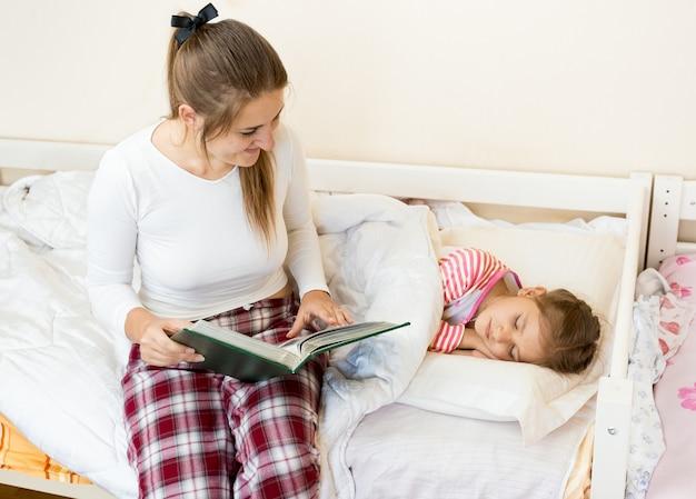 Jeune mère assise sur le lit à côté de sa fille et lisant une histoire