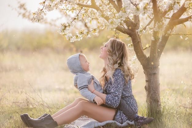 Jeune mère aux cheveux bouclés embrasse petit fils, assis dans l'herbe verte près de cerisier blanc en fleurs