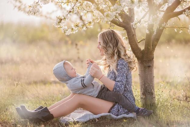 Jeune mère aux cheveux bouclés embrasse son fils, assis dans l'herbe verte près de cerisier blanc en fleurs